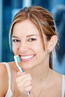 Beautiful woman holding a toothbrush in front of her face