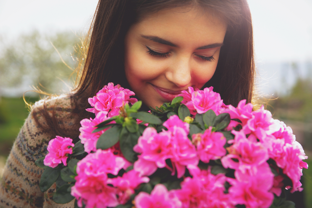 Young cute woman smelling pink flowers